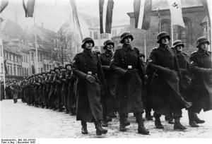 Lettland beging seinen Nationalfeiertag. Anlässlich der 25. Wiederkehr des lettischen Nationalfeiertages [18.11.?] fand ein Standortappell der Einheiten der lettischen Freiwilligen-SS-Legion statt. UBz. die Formationen der Legion auf dem Wege zum Appellplatz. Bei Abdruck nennen: Scherl Bilderdienst, 2.12.43 [Herausgabedatum] 532-43